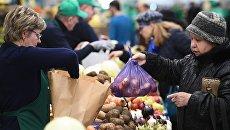 Посетители у торговых рядов на рынке. Архивное фото