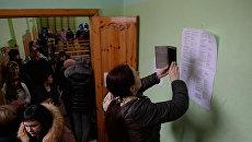 Женщина фотографирует на мобильный телефон списки пропавших без вести при пожаре в торговом центре «Зимняя вишня» в Кемерово