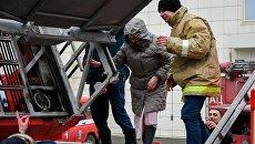 Сотрудники пожарной охраны МЧС помогают посетителям выбраться из торгового центра Зимняя вишня в Кемерово, где произошел пожар