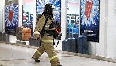 Сотрудник противопожарной службы у эвакуационного выхода во время учений в торговом центре