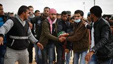 Палестинские протестующие несут пострадавшего во время столкновений с израильскими военными на границе сектора Газа и Израиля. Архивное фото