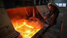 Рабочий в цехе электролиза на алюминиевом заводе. Архивное фото