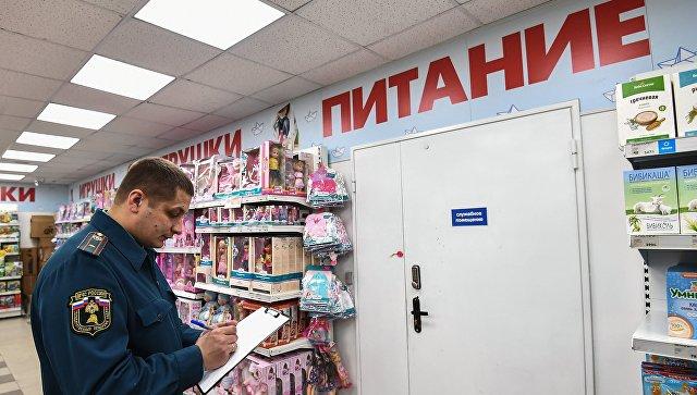 Сотрудник государственного пожарного надзора во время проверки пожарной безопасности в торгово-развлекательном центре