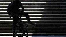 Мужчина на велосипеде в подземном переходе в Москве