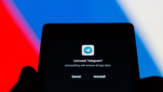 Логотип Telegram на экране смартфона на фоне флага РФ
