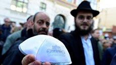 Мужчина показывает традиционную еврейскую кипу на мероприятии Berlin wears kippa в Берлине