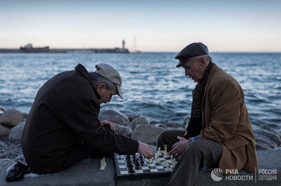 Мужчины играют в шахматы на набережной в Ялте