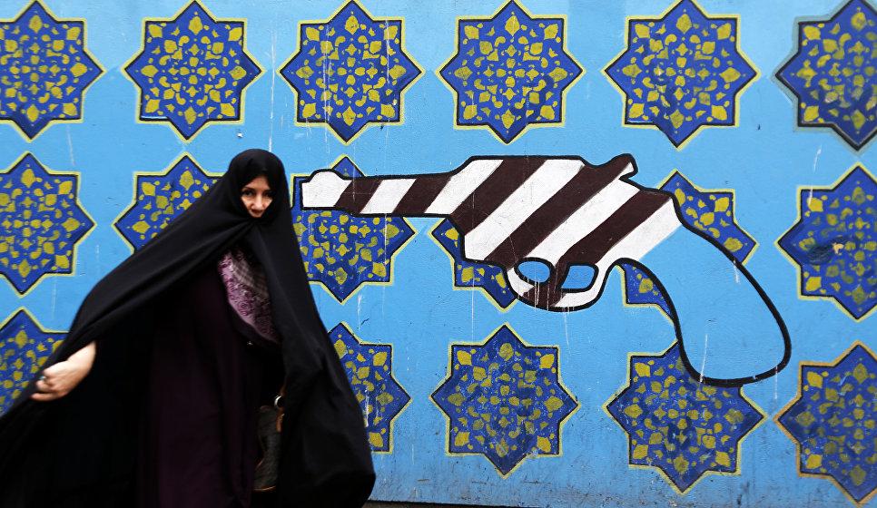 Иранская женщина проходит мимо граффити на стене бывшего посольства США в Тегеране