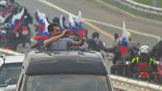 Путешественники приветствовали друг друга, впервые проезжая по Крымскому мосту