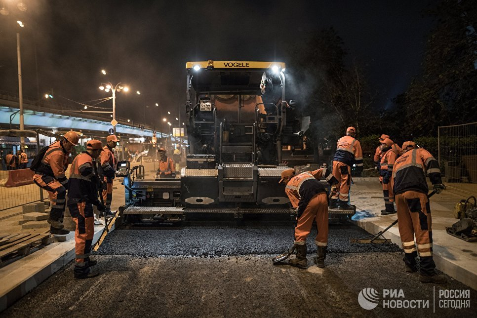 Рабочие во время укладки асфальта возле главного входа ВДНХ в Москве. 17 мая 2018