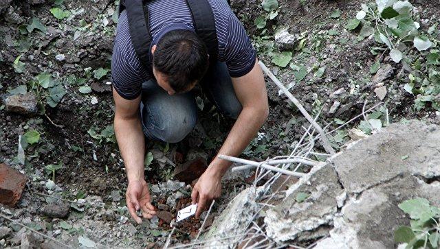 Представители наблюдательной группы СЦКК «Горловка» собирают осколки от снарядов в поселке Горловка Донецкой области. Архивное фото