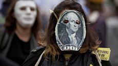Девушка в маске, стилизованной под стодолларовую банкноту. Архивное фото