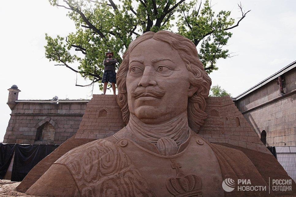 Мастер у скульптуры во время подготовки к открытию фестиваля песчаных скульптур в Санкт-Петербурге