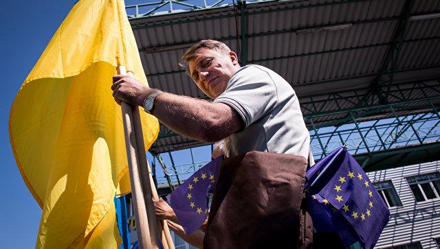 Мужчина с флагами Украины и Евросоюза на границе Словакии и Украины в районе КПП Ужгород-Вишне-Немецкое. Архивное фото