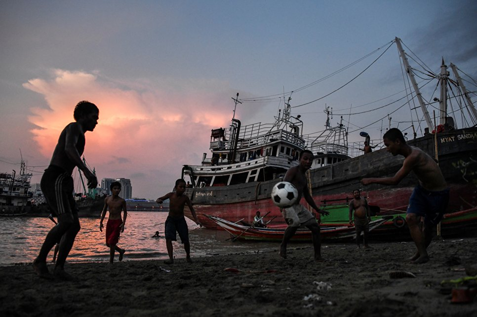 Молодежь играет в футбол на берегу реки Янгон, Мьянма