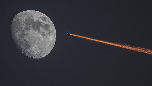 Луна и самолет на закате. Архивное фото