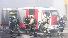Сотрудники МЧС и пожарная техника перед зданием торгового центра Порт в Казани, где произошло возгорание