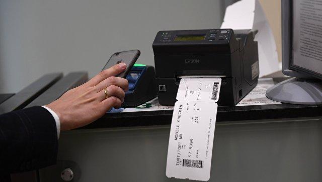 Пассажир сканирует и распечатывает посадочный талон в аэропорту. архивное фото