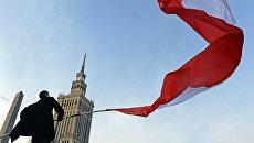 Мужчина держит польский флаг в Варшаве. Архивное фото