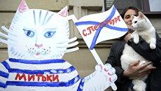 Девушка и эрмитажный кот-оракул Ахилл рядом с фигурой кота-футболиста, расписанной в рамках художественного марафона Моя любовь - футбол и кот! в Санкт-Петербурге. Архивное фото