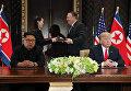 Лидер КНДР Ким Чен Ын и президент США Дональд Трамп во время подписания документов по итогам встречи в Сингапуре. 12 июня 2018