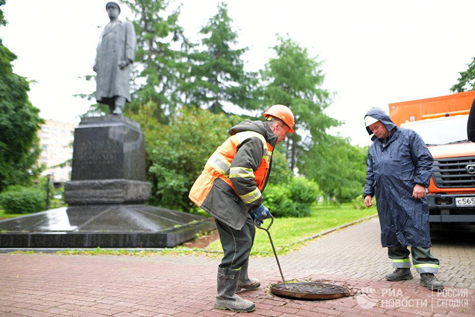 Сотрудники ГУП Мосводосток проверяют смотровой колодец