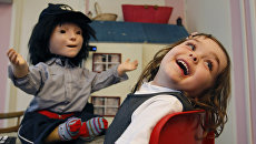 Девочка играет с социальным роботом Каспаром, созданным в качестве терапии для детей-аутистов