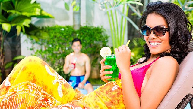 Женщина с коктейлем у бассейна