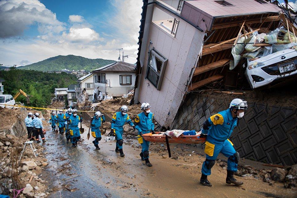 Спасатели в районе наводнения в Кумано, префектура Хиросима, Япония. 9 июля 2018 года