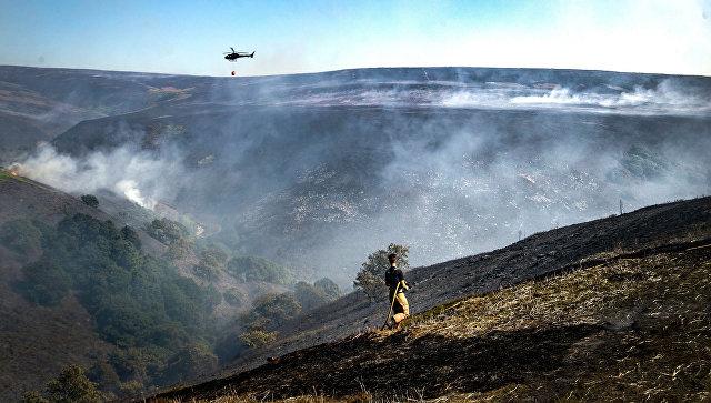 Пожарный во время пожара в приходе Садлворт, Великобритания