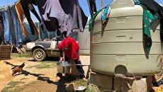 Женщина набирает воду в палаточном лагере для сирийских беженцев в Ливане. Архивное фото