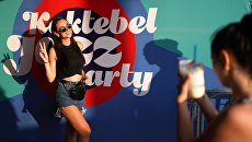 Девушка фотографируется у баннера музыкального фестиваля Koktebel Jazz Party 2018