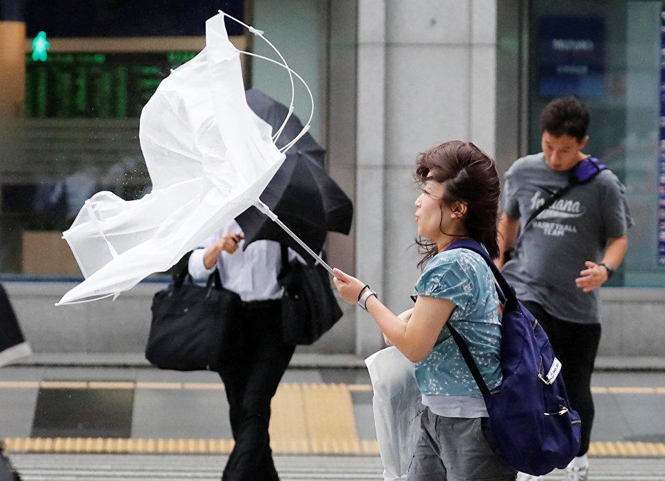Девушка идет с зонтом во время сильного ветра, вызванного тайфуном Джеби, Токио, Япония
