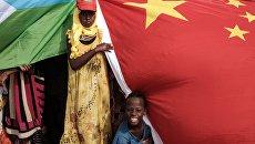 Жители Джибути с национальными флагами Китая и Республики Джибути. Архивное фото
