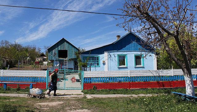 Жительница села Льговка Судакского района Крыма возвращается домой от уличной колонки, в которой нет воды. 2014 год