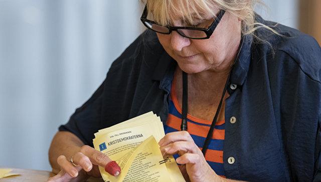 Женщина  подсчитывает  бюллетени по итогам парламентских выборов в одном из округов Стокгольма, Швеция. 13 сентября 2018
