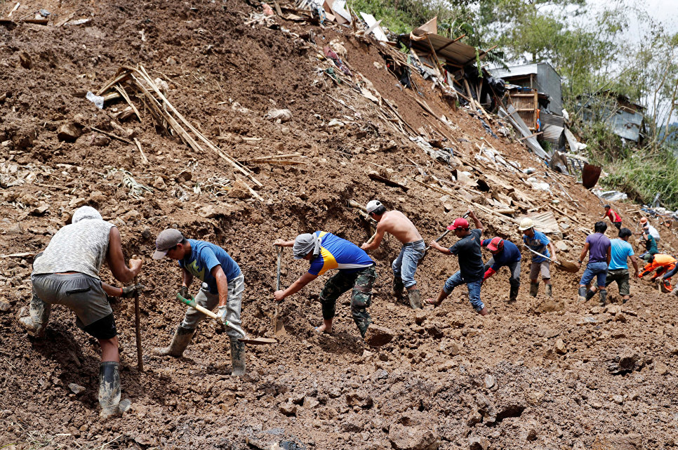 Спасатели филиппинского города Итогон на месте схода оползня, вызванного тайфуном Мангхут. 17 сентября 2018 года