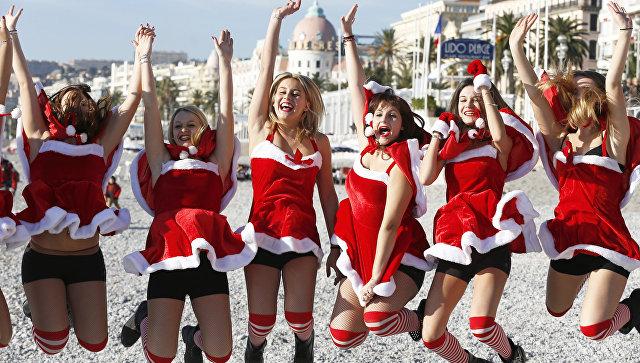 Девушки в костюмах Санта-Клаусов на пляже в Ницце, Франция