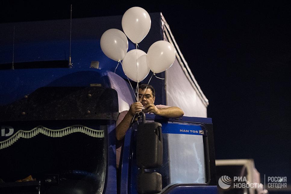 Водитель грузовой машины, украшает шариками кабину перед первым проездом по Керченскому мосту