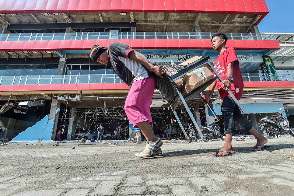 Люди несут товары из торгового центра после землетрясения и цунами в городе Палу, на острове Сулавеси, Индонезия. 30 сентября 2018 года