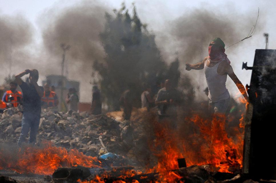 Палестинские демонстранты во время акции протеста у израильского поселения Бейт-Эль
