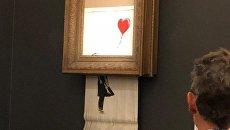 Работа художника Бэнкси Девочка с шаром во время самоуничтожения на аукционе Sotheby's в Лондоне