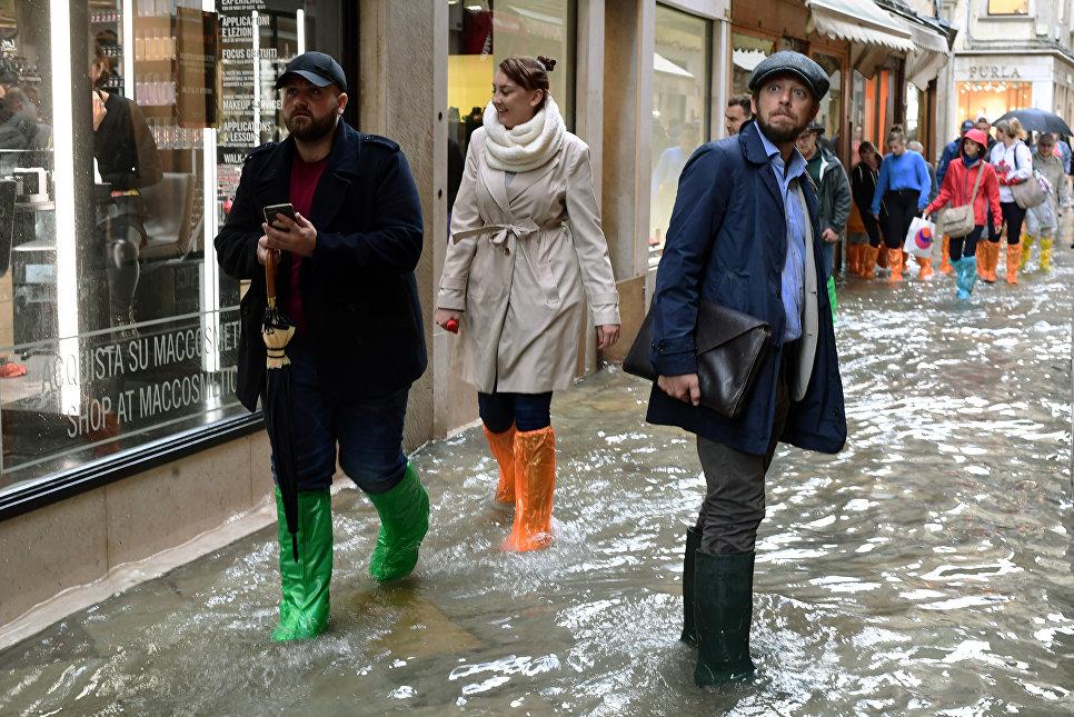 Туристы гуляют по затопленным улицам возле моста Риальто во время сезонного половодья в Венеции, Италия. 29 октября 2018 года
