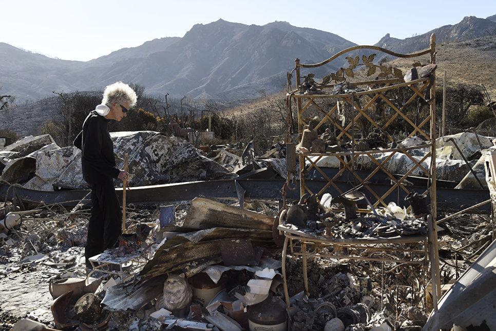 Женщина стоит на месте сгоревшего дома в Калифорнии, США