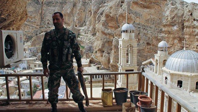 Военнослужащий сирийской армии на фоне церкви в городе Маалюля. Архивное фото