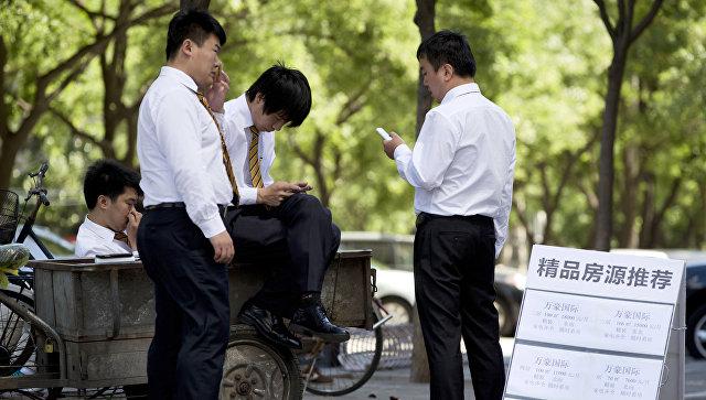 Офисные работники во время перерыва на улице Пекина, КНР. Архивное фото