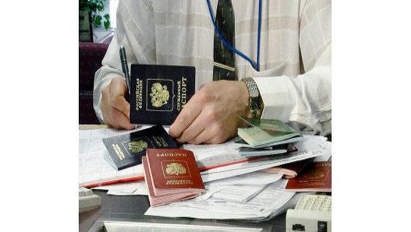 Сотрудник посольства проверяет паспорта российских граждан. Архивное фото
