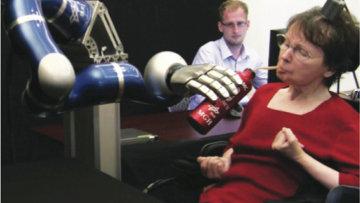 Женщина-инвалид пьет кофе при помощи кибернетической руки. Архив