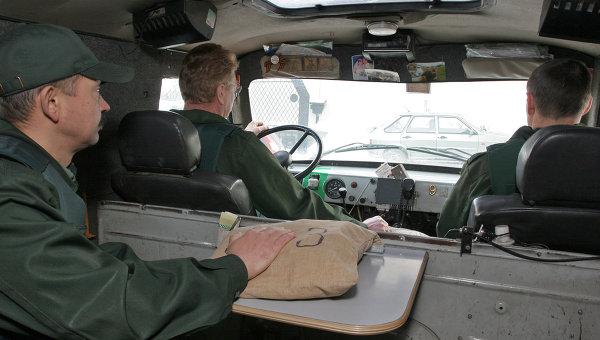 Сотрудники Акционерного коммерческого банка обеспечивают перевозку ценностей в бронированном автомобиле.
