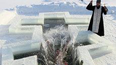 Мужчина купается в проруби, вырезанной в форме православного креста